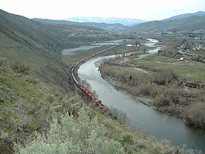 """I want to see it as ordinary, to strip myself of sentimentality and see clearly at last."" Looking upstream from the hills of northwest Wenatchee; a train hauling containers runs along the Wenatchee River."